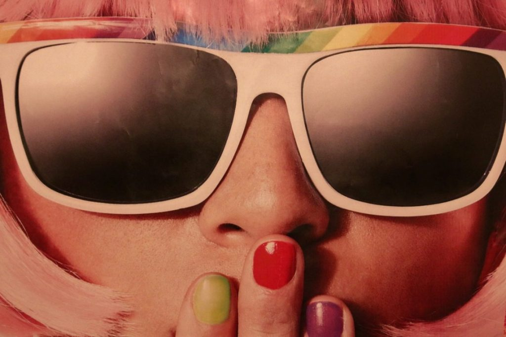 female with sunglasses and colourful nails