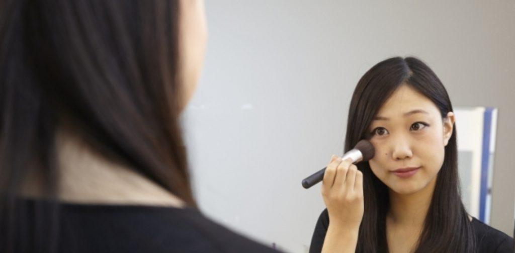 female applying blush onto cheeks