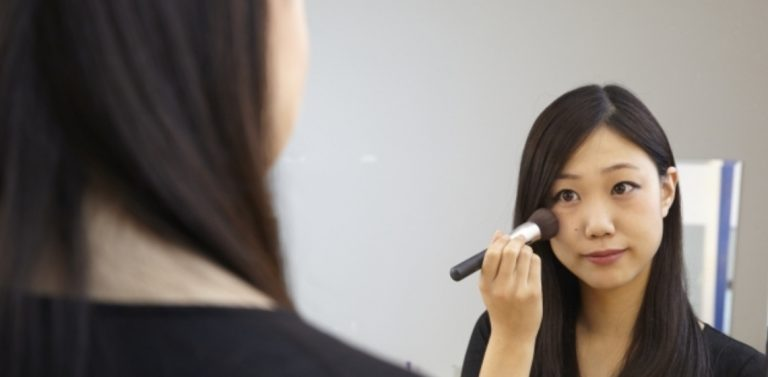 female applying blush onto cheeks