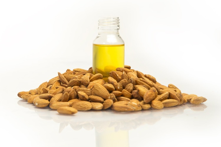 bottle of almond oil with fresh almonds