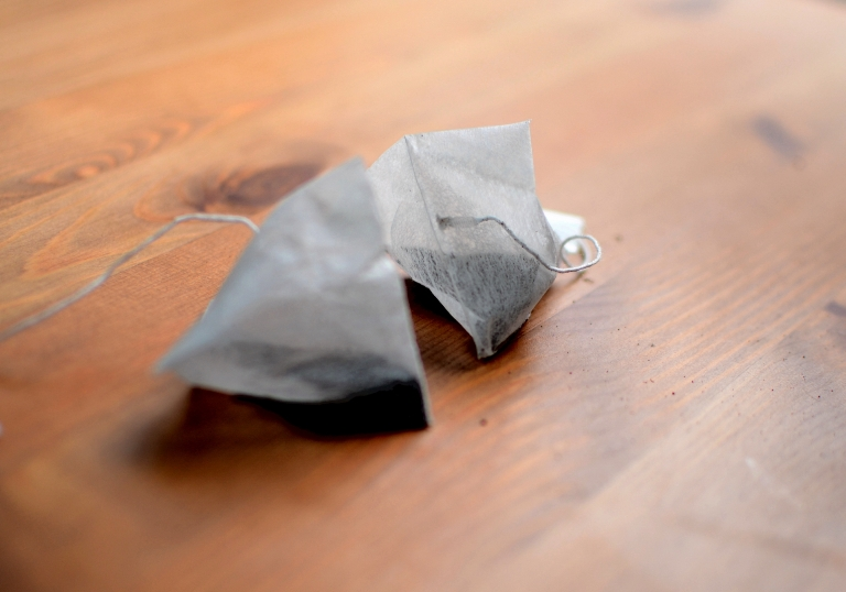 two tea bags on wooden surface