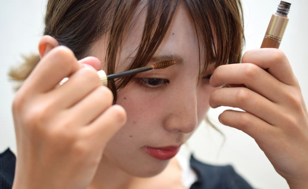 female applying eyebrow mascara